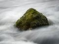 En ensam liten sten i det forsande vattnet. Försökte hitta en tid det man kunde se rörelsen som omgav stenen