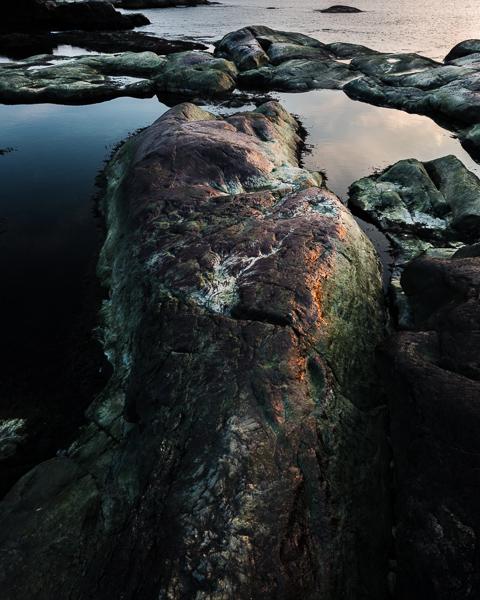Gröna klippor och solnedgången som speglar sig