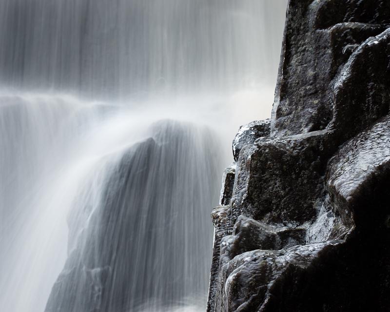 Vatten och svarta klippstenar